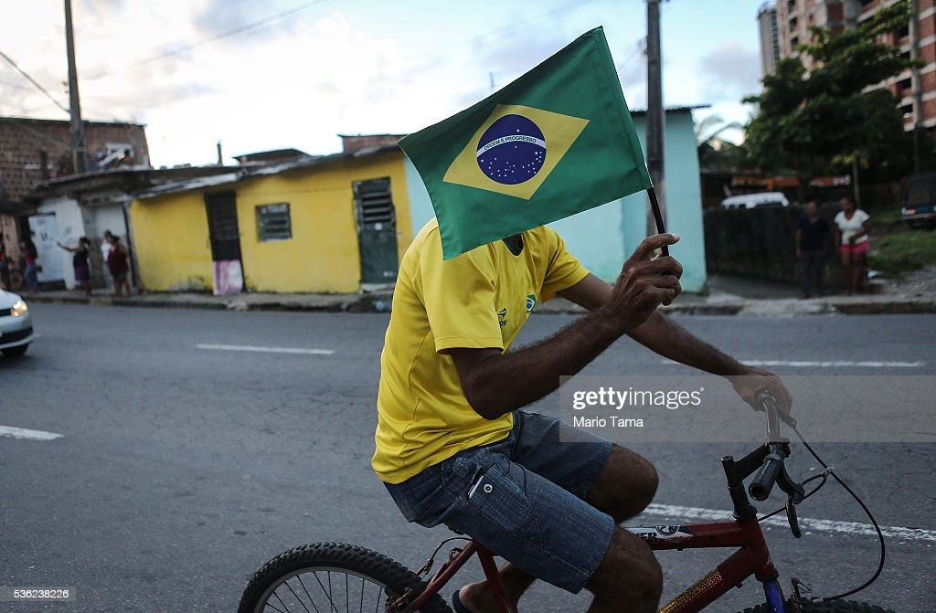 A cyclist carries the Brazilian flag along the Olympic torch route on May 31, 2016 in Recife, Brazil. The Olympic flame will pass through 329 cities from all states from the north to the south of Brazil, before arriving in Rio de Janeiro on August 5, for the lighting of the cauldron for the Rio 2016 Olympic Games. The games will be held amidst an economic and political crisis in the country.