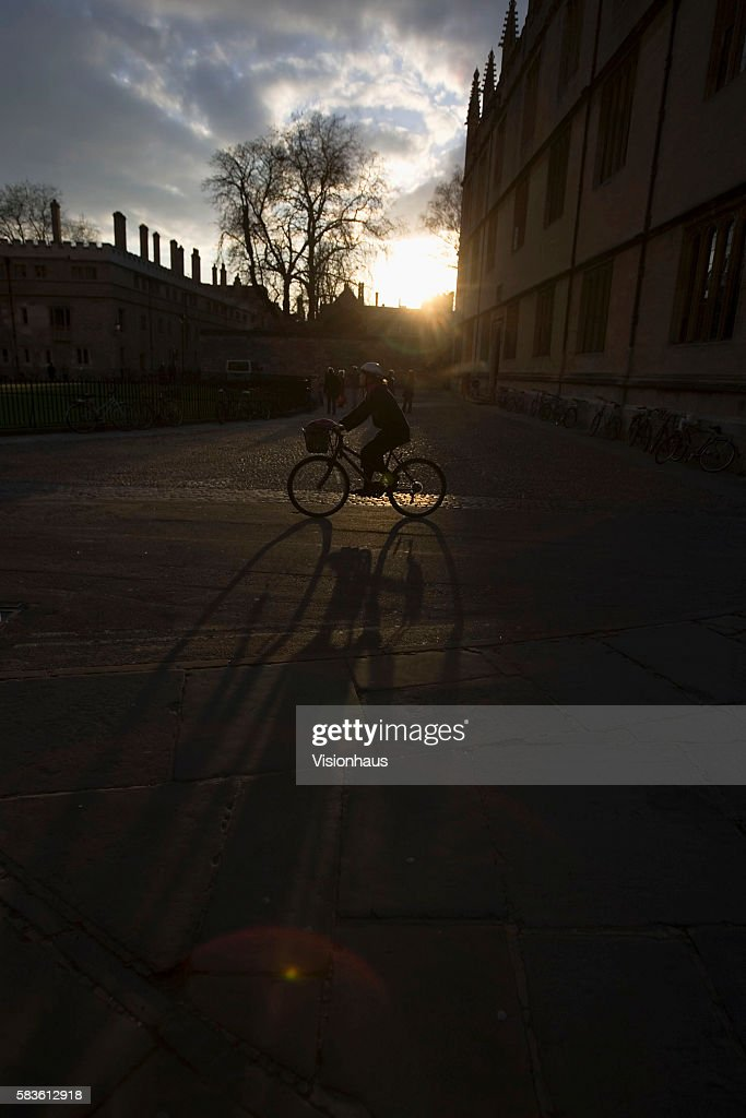 Cyclist casting a shadow in Radciffe Square as she passes the Bodleian Library in Oxford Affectionately named 'the city of dreaming spires' by...