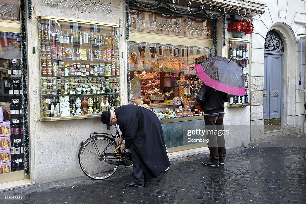 A cyclist chains his bicycle as a pedestrain looks at the window display of a delicatessen near Campo dei Fiori market in Rome, Italy, on Monday, Dec. 10, 2012. The imminent end of Prime Minister Mario Monti's government fueled the largest increase in Italian borrowing costs in four months and threatened to open a new front in Europe's crisis fight before a year-end summit. Photographer: Victor Sokolowicz/Bloomberg via Getty Images