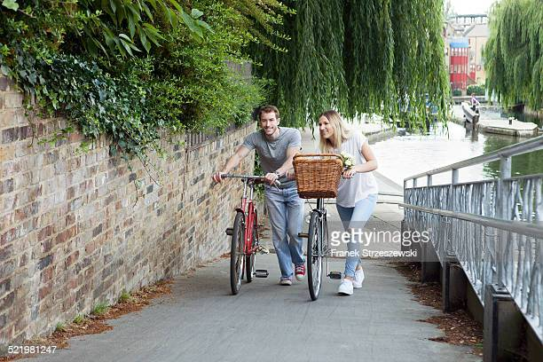 Cyclist couple pushing bike along canal, London, UK