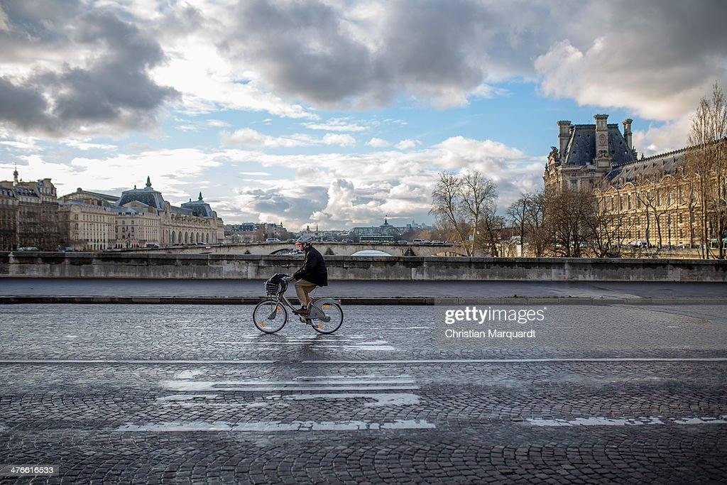 A cyclist crosses the bridge Carousel with Louvre on the right hand during a rainy day on February 28, 2014 in Paris, France. The museum is housed in the Louvre Palace, one of the world's largest museums which opened 1793.