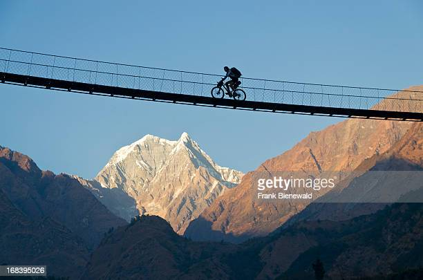 A cyclist crossing a suspension Bridge over Kali Ghandaki Valley on the Annapurna Circuit in Nepal which is regarded as one of the finest treks in...