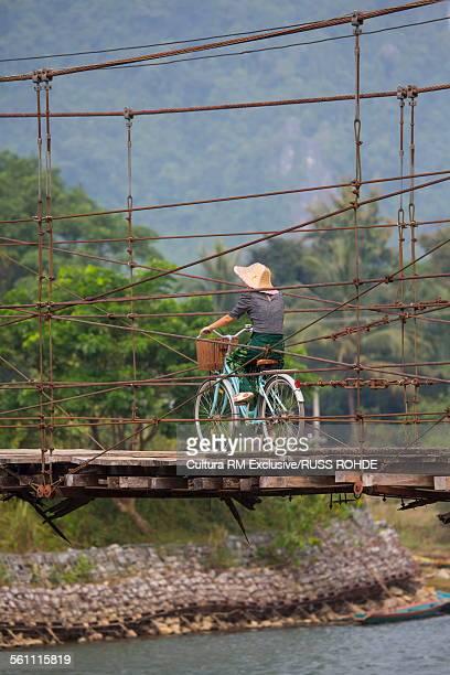Cyclist crossing old bridge over Nam Song River, Vang Vieng, Laos