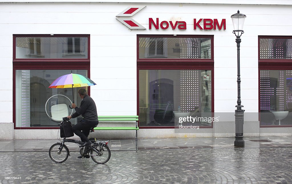 A cyclist cycles with an umbrella past a Nova Kreditna Banka Maribor d.d. (KBM) bank branch in Ljubljana, Slovenia, on Monday, May 6, 2013. Slovenia plans to increase taxes to make up for the swelling budget shortfall as the country works to recapitalize its banks. Photographer: Chris Ratcliffe/Bloomberg via Getty Images