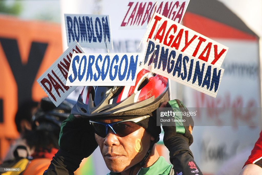 A cyclist decked in headgear detailing different locations in the Philippines rides in the streets during the annual Tour of the Fireflies cycling event on November 18, 2012 in Manila, Philippines. The annual event organized by the Firefly Brigade, a cycling group of environmentalists, aims to promote cycling as a sustainable form of transportation in Metro Manila and has become a rite of passage for a growing number of weekend cyclists from all walks of life.