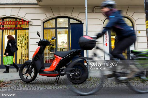 A cyclist drives past a scooter of the sharing agency Emmy on November 13 2017 in Berlin Germany A number of companies have plunged into the market...