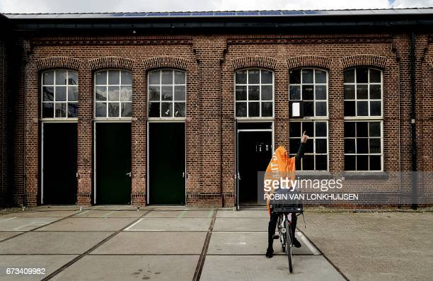 A cyclist gestures as he wears an orange banner ahead of the King's Day celebrations in Tilburg on April 26 2017 / AFP PHOTO / ANP / Robin van...