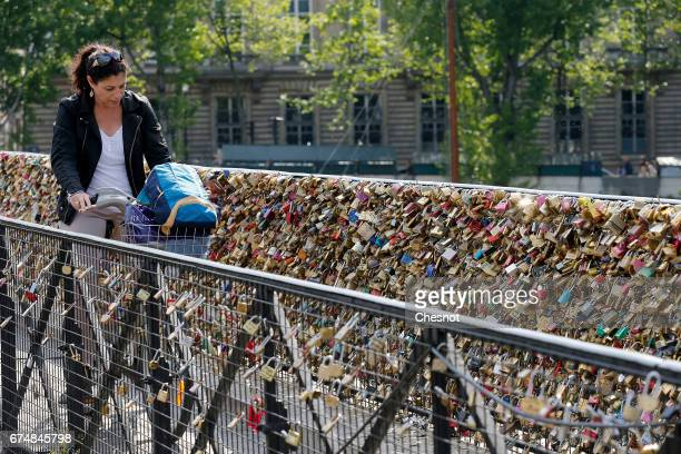 A cyclist goes past love padlocks on the Pont Neuf on April 29 2017 in Paris France The Paris City Hall will organize on May 13th an auction of love...