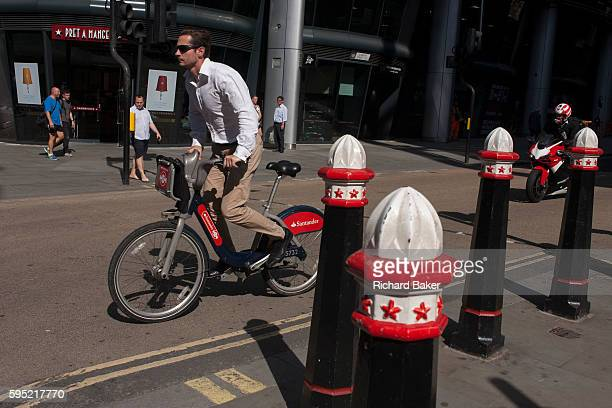 A cyclist has hired a public bike sponsored by Santander and rises off his saddle and pedals past traffic bollards on Cannon Street on 24th August...