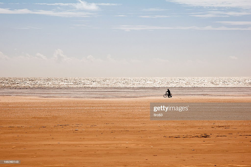 Cyclist in silhouette on the beach : Stock Photo