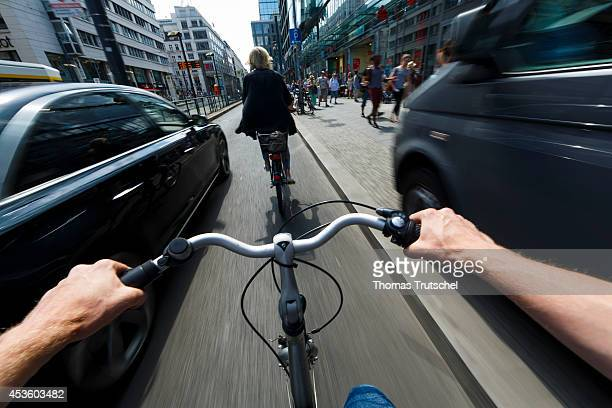 Cyclist is being overtaken by a car which does not keep a safe distance on August 05 in Berlin Germany Pedestrians and cyclists are particularly at...