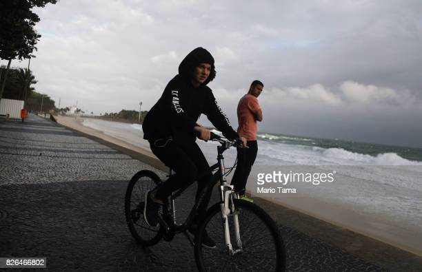 A cyclist is bundled up against the cold on Ipanema beach in the midst of a winter cold front on August 4 2017 in Rio de Janeiro Brazil Temperatures...