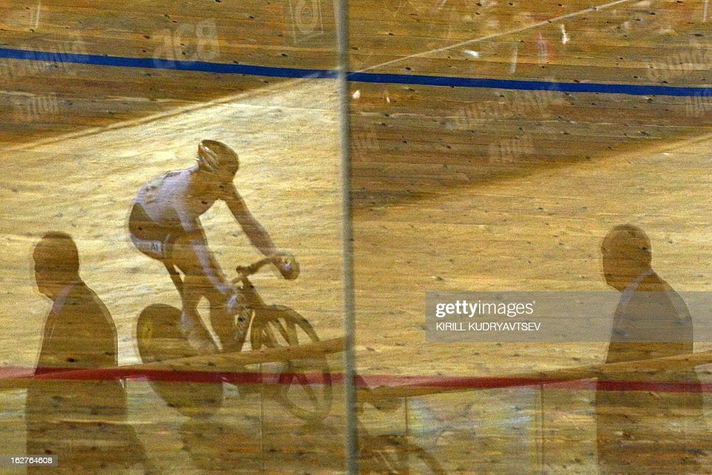 A cyclist is reflected in the track's cover as he competes during UCI Track Cycling World Championships Men's 40 km Point Race in the Belarus capital Minsk on February 22, 2013.