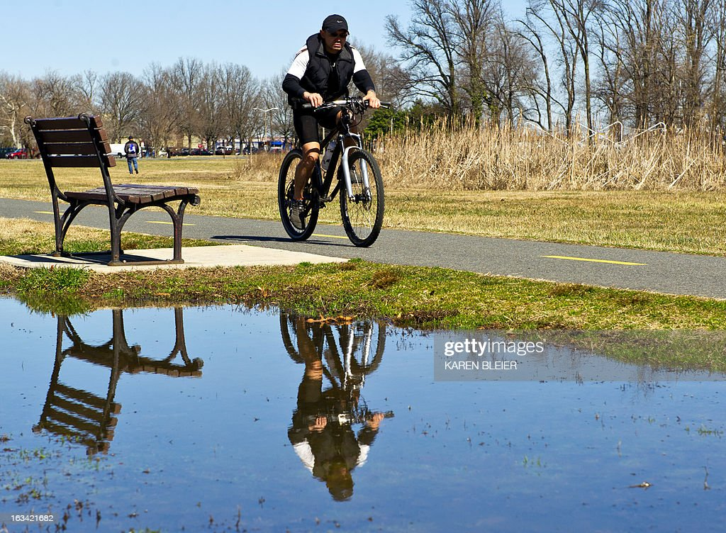A cyclist is reflected in water as he rides on a warm sunny day in Alexandria, Virginia, on March 9, 2013. The weather was in stark contrast to that of only a couple of days ago, when a winter storm hammered the East coast. AFP PHOTO / Karen BLEIER