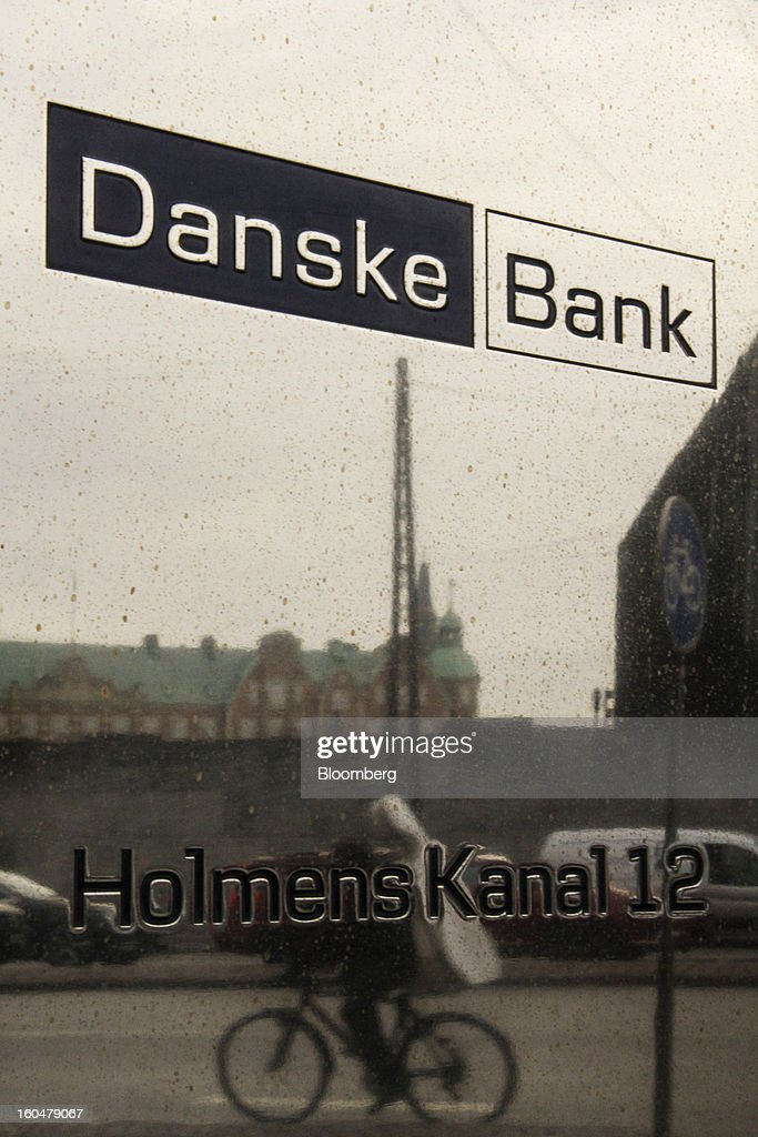 A cyclist is reflected on a sign outside the headquarters of Danske Bank A/S in Copenhagen, Denmark, on Friday, Feb. 1, 2013. Danish regional banks are struggling to emerge from a burst property bubble that's forced the government resolution agency to take over a dozen lenders after losses on commercial and agricultural loans wiped out capital. Photographer: Freya Ingrid Morales/Bloomberg via Getty Images