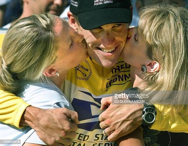 US cyclist Lance Armstrong is kissed by his wife Linda and mother after winning the Tour De France cycling race in Paris 25 July 1999
