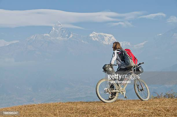 A cyclist leaning on his bike looking towards Annapurna range rests on the Annapurna Circuit in Nepal which is regarded as one of the finest treks in...