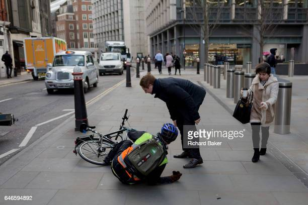 A cyclist lies shocked on the pavement after being blown over as Storm Doris blows across the UK and pedestrians on Fenchurch Street brave the high...