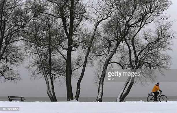 A cyclist makes his way through the snowy landscape at Ammersee lake near Herrsching southern Germany on December 1 as winter weather brought...