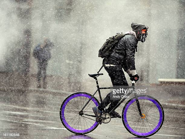 A cyclist makes their way across Broadway at 17th Ave in a light snow storm Tuesday morning January 24th 2012 in downtown Denver Andy Cross The...