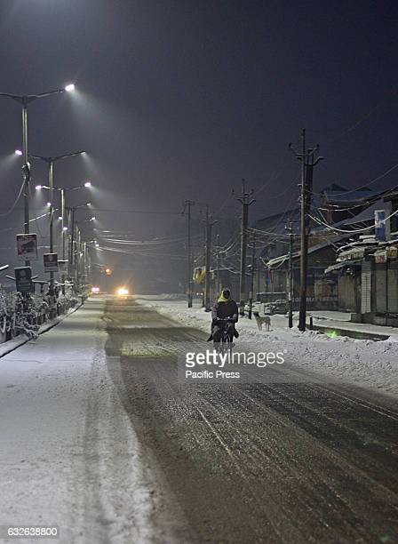 A cyclist moves early morning after the fresh snowfall in Srinagar the summer capital of Indian controlled Kashmir on January 25 2017Normal life in...