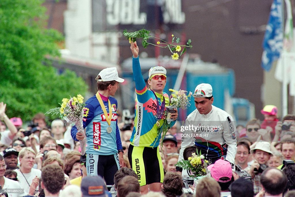 US cyclist Nate Reiss throws flowers to the crowd after his victory on May 6, 1990 in the Richmond to Charlottesville road race of the Tour de Trump. At left is Atle Kvolsvoll of Norway, who finished second and at right Mexican cyclist Raul Alcala who finished third. / AFP / Don EMMERT