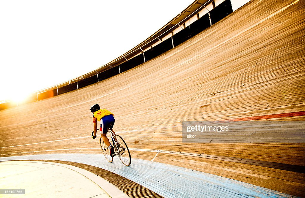 Cyclist on a velodrome track riding towards the evening sun