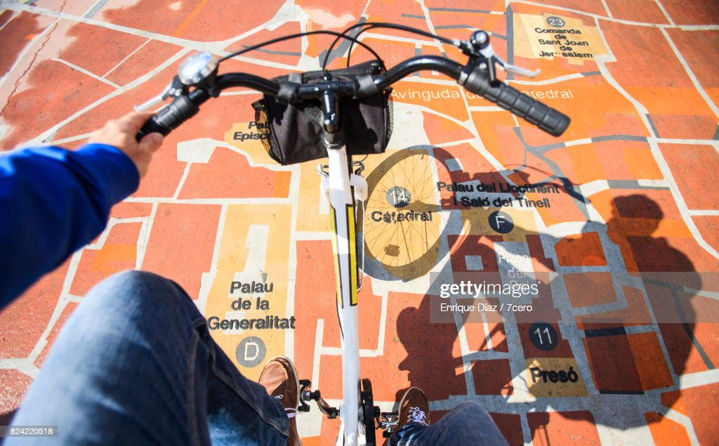 Silhoutte and point of view shot of a cyclist looking for directions on a public map of Barcelona in the city centre.