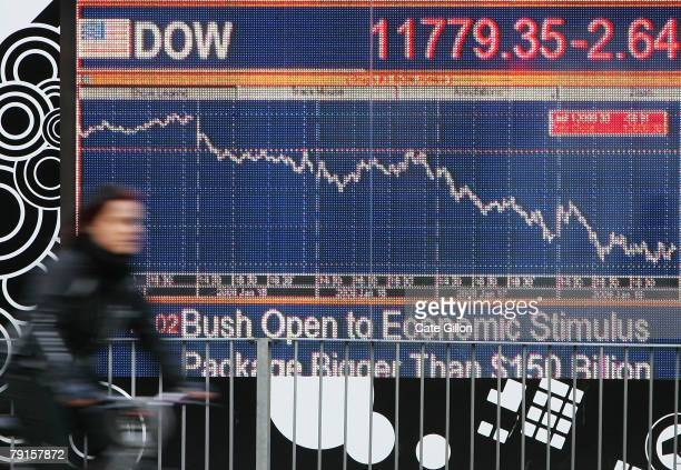 A cyclist passes a financial display screen showing the FTSE 100 on January 22 2008 in West London Widespread fears of a global recession have...