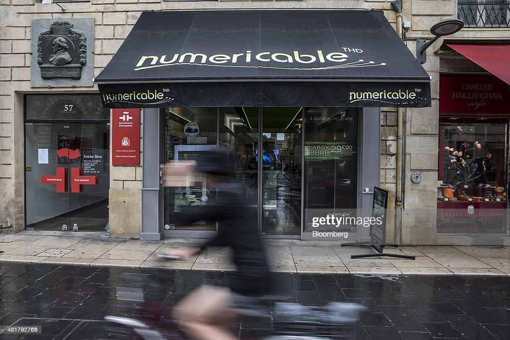 A cyclist passes a Numericable Group SA cable-television and internet store, operated by Altice SA, in Bordeaux, France, on Friday, July 4, 2014. Altice is raising its stake in Numericable after agreeing in April to merge the French cable provider with Vivendi SA's phone unit SFR, a transaction valued at more than 17 billion euros. Photographer: Balint Porneczi/Bloomberg via Getty Images