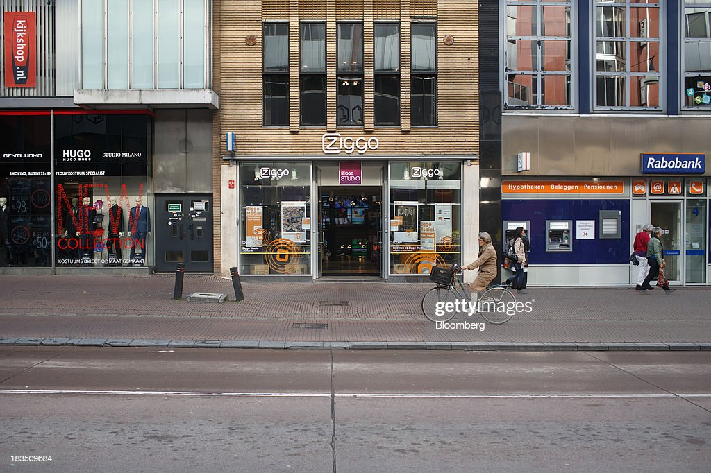 A cyclist passes a Ziggo NV store, center, and a Rabobank Groep NV bank branch in Utrecht, Netherlands, on Friday, Oct. 4, 2013. Cable-TV provider Ziggo, which is 28.5 percent owned by Liberty Global Plc, is pushing into the Dutch mobile market with low-priced packages, following a playbook pioneered by French discount operator Iliad SA. Photographer: Jasper Juinen/Bloomberg via Getty Images