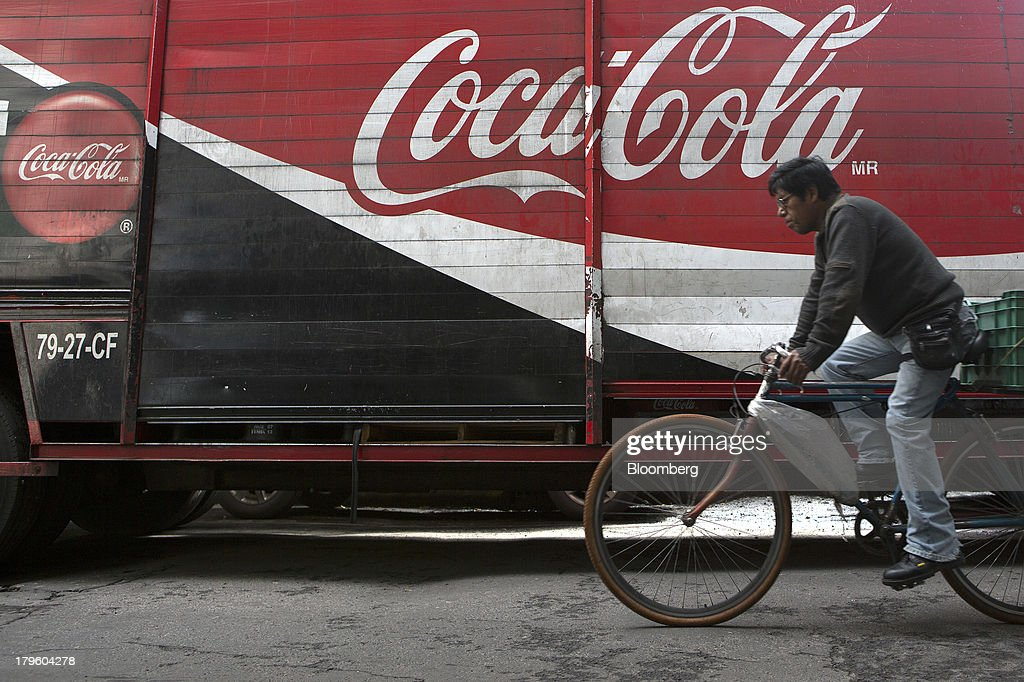 A cyclist passes by a Coca-Cola delivery truck in Mexico City, Mexico, on Thursday, Sept. 5, 2013. Coca-Cola Femsa SAB, a bottler and distributor of Coca-Cola products in Mexico, agreed to buy Brazils Spaipa SA Industria Brasileira de Bebidas in a cash deal with a total transaction value of $1.86 billion. Photographer: Susana Gonzalez/Bloomberg via Getty Images