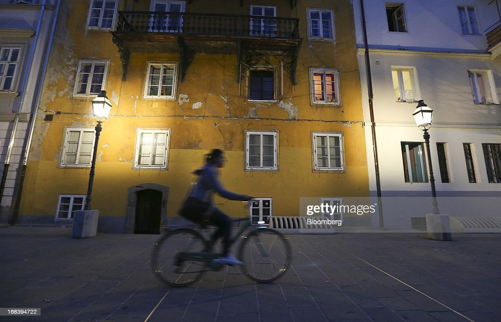 A cyclist passes residential buildings illuminated by street lights in Ljubljana, Slovenia, on Wednesday, May 8, 2013. Slovenia's recession will stretch into next year on weak domestic demand as the euro-area country teeters on the brink of needing an international bailout, the European Commission said. Photographer: Chris Ratcliffe/Bloomberg via Getty Images