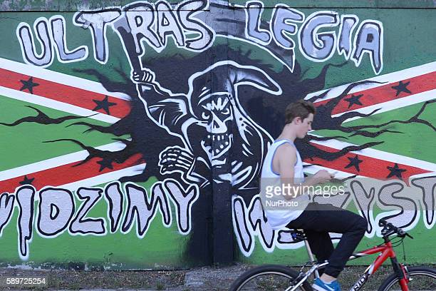 A cyclist passes the famous graffiti wall over 1km long openair gallery of graffiti located at the racecourse in Sluzewiec The fence have many holes...