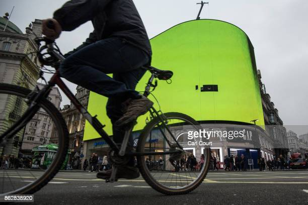 A cyclist passes the Piccadilly Circus billboard as it displays a test screen on October 18 2017 in London England After nine months of works to...