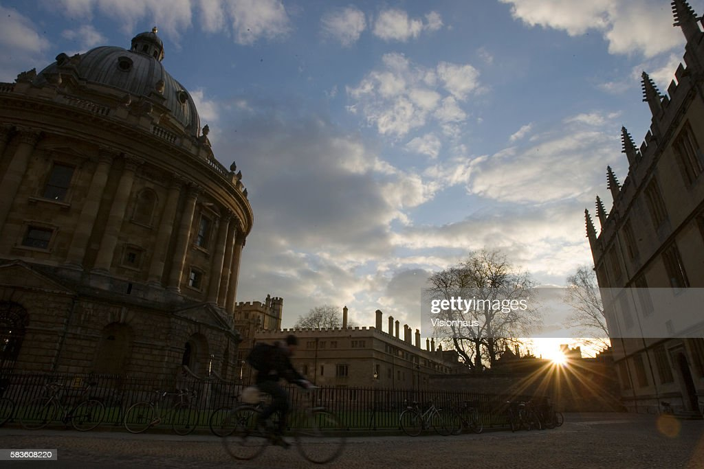 Cyclist passes the Radcliffe Camera and the Bodleian Library in Radcliffe Square Oxford at sunset Affectionately named 'the city of dreaming spires'...