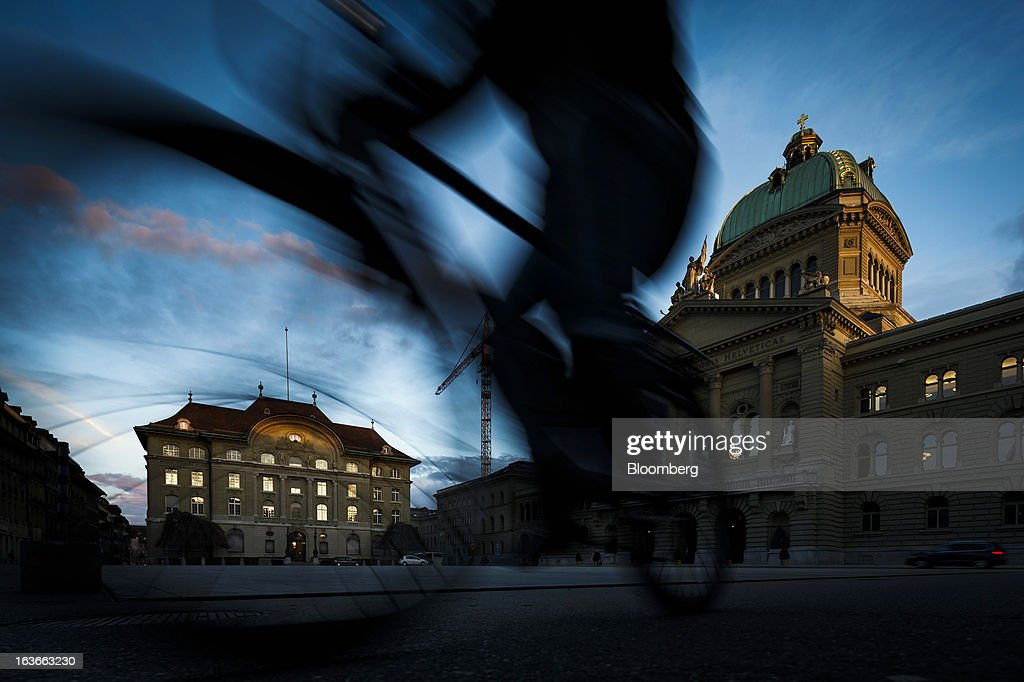 A cyclist passes the Swiss National Bank (SNB), Switzerland's central bank, left, and the Federal Palace, Switzerland's parliament building in Bern, Switzerland, on Tuesday, March 12, 2013. The Swiss central bank pledged to keep up its defense of the franc cap after almost doubling its currency holdings to shield the country from the fallout caused by the euro zone's crisis. Photographer: Valentin Flauraud/Bloomberg via Getty Images
