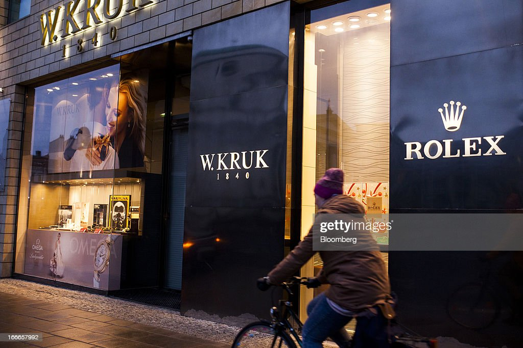 A cyclist passes the window displays of a W. Kruk jewelry store advertising Rolex watches in Warsaw, Poland, on Thursday, April 11, 2013. Poland's central bank kept interest rates unchanged at a record-low 3.25 percent yesterday. Photographer: Bartek Sadowski/Bloomerg