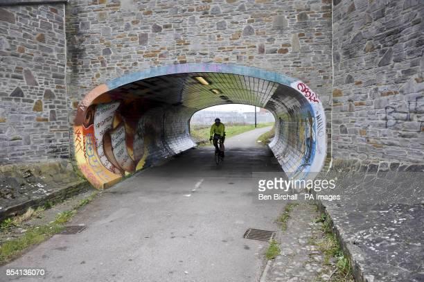 A cyclist passes through a graffiti covered subway bridge on the Bristol Bath railway path in a section through Fishponds Bristol The Bristol Bath...