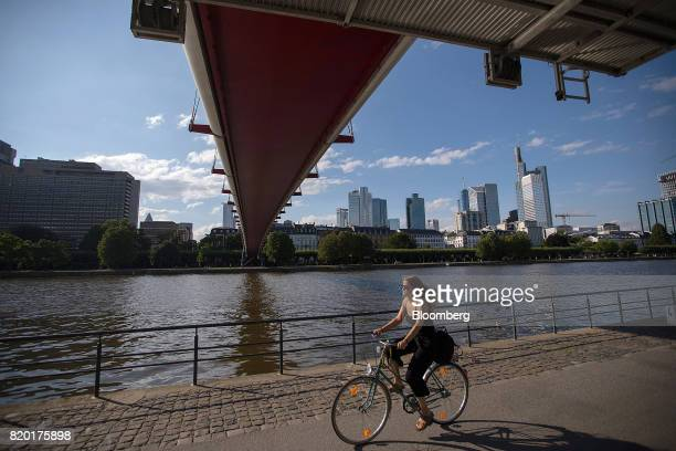 A cyclist passes under a bridge spanning the River Main as skyscrapers stand beyond in Frankfurt Germany on Thursday July 20 2017 Frankfurt has...