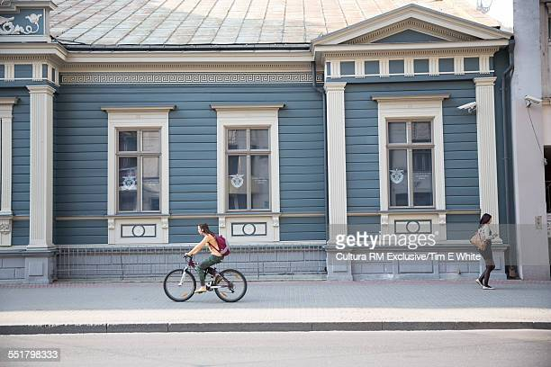 Cyclist passing traditional blue painted building, Riga, Latvia