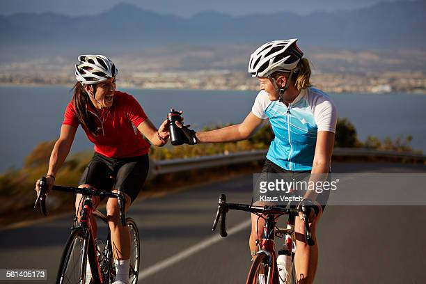 Cyclist passing water bottle to training partner