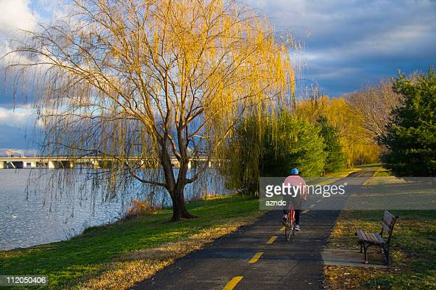 Cyclist pedaling down bike trail next to the Potomac at dawn