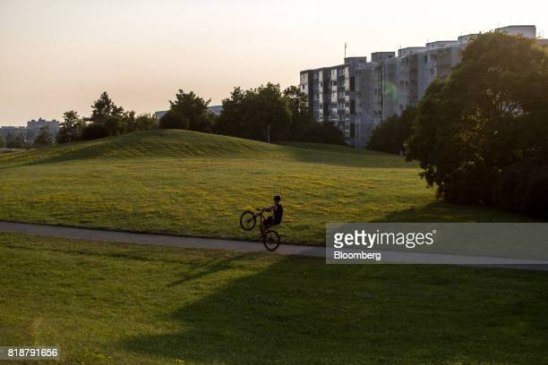 A cyclist performs a wheelie in the park as concrete highrise residential apartment blocks stand beyond in the 'South city' district of Prague Czech...
