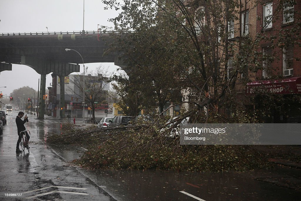 A cyclist photographs a fallen tree in the Gowanus neighborhood of Brooklyn in New York, U.S., on Monday, Oct. 29, 2012. Hurricane Sandy, the Atlantic's Ocean's biggest-ever tropical storm, barreled toward southern New Jersey after bringing a region with 60 million residents to a virtual standstill and upending the U.S. presidential race eight days before Election Day. Photograph: Victor J. Blue/Bloomberg via Getty Images