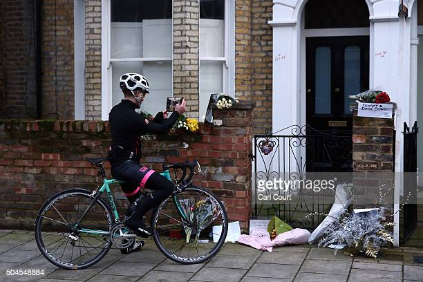 A cyclist photographs flowers and tributes left outside the boyhood home of David Bowie in Brixton on January 11 2016 in London England British music...