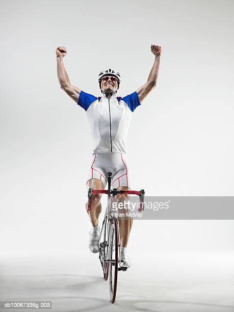 Cyclist pumping fists, studio shot