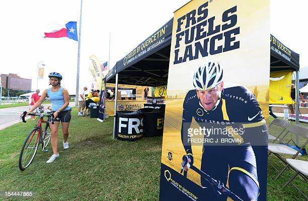 A cyclist pushes her bike past an advertising banner with an image of banned US cyclist Lance Armstrong as riders check out the course a day ahead of...