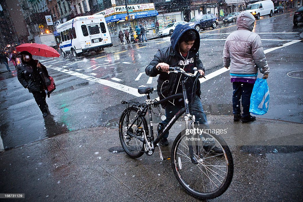 A cyclist pushes his bike through a winter snowstorm on December 26, 2012 in New York City. Snow, mixed with and changing to rain, is expected to hit the New York City area this afternoon into the evening.