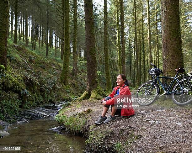 Cyclist resting beside stream in woodland.